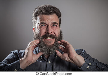 Scratching huge beard portrait, mature adult Caucasian man -...