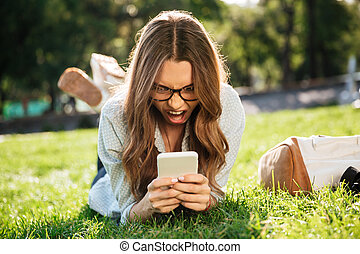 Screaming angry brunette woman in eyeglasses lying on grass