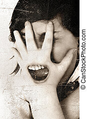 Communication concept image, teen girl screaming with mouth over hand covering face.