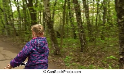 The girl screams coolly, in the spring forest. Riding a bike on the road, the camera accompanies her