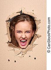 Screaming girl peeping through hole in paper