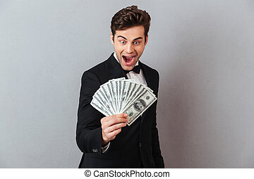Screaming man in official suit holding money.