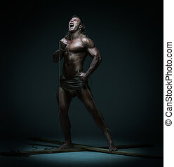 Screaming muscular man, hands tied rope to wooden beams