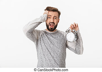 Screaming scared young man holding alarm clock.