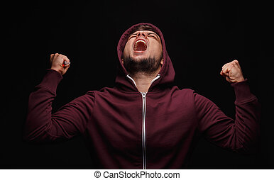 Screaming, sick male on a black background. Stressed student in a hoodie. Man suffering in pain. Anger issues concept.