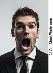 Screaming - Young man screaming surprised looking at camera.