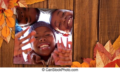 Screen with autumn leaves on corners showing a happy family waving hands