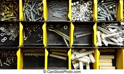 Screw and dowel in plastic organizer box. fasteners