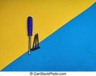 screw driver with self-tapping screws on a yellow-blue background with a copy space.