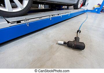 screwdriver and car at tire shop