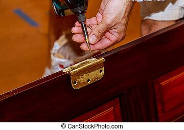 Screwdriver installs screw on stainless door hinges with wooden swing door