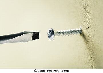 Screwing a screw in a wall with a screwdriver