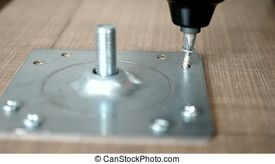 Screwing a screw with an electric screwdriver. Close up slow...