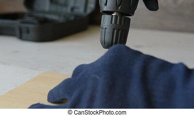 Screwing a screw with electric screwdriver. Repair of a...