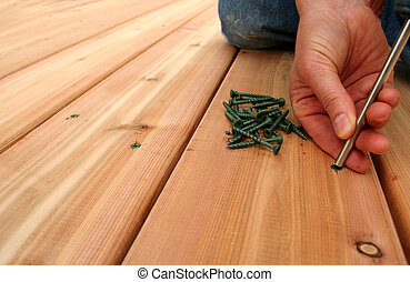A hanywoman screws on new cedar decking. Copy space on left.
