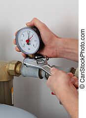 Screwing pressure gauge - Man's hands screwing pressure...