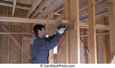 Screwing the screw in a wooden board. The worker in the...