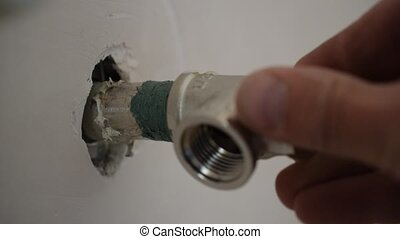 Closeup of plumber screwing up manually a pipe T-joint fitting connector onto pipe end in wall with hemp and sealant threat