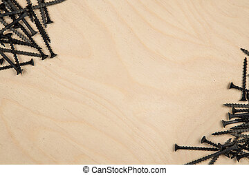 Screws on diagonal of wood plate. Construction background with tools.