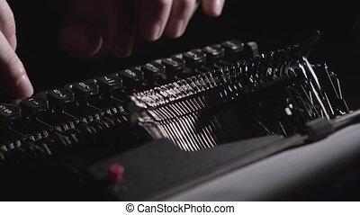 Script writer prints the text on a typewriter - Dark room,...