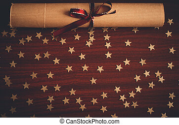 Scroll of paper with brown ribbon and lots of small gold star confetti on the wooden table top view flat lay