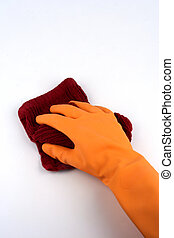 Gloved hand holding rag with cleaning bottle in background