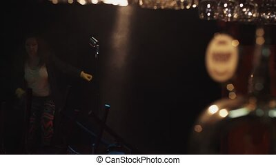 Scrubwoman in gloves run from stage in empty club. Turn off...