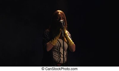 Scrubwoman in gloves sing at vintage microphone on stage under spotlight.
