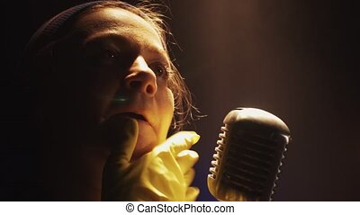 Scrubwoman in gloves start sing in vintage microphone on stage. Spotlight.