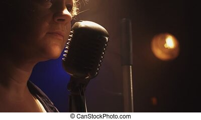 Scrubwoman scream in vintage microphone on stage of club. Smoke. Spotlight