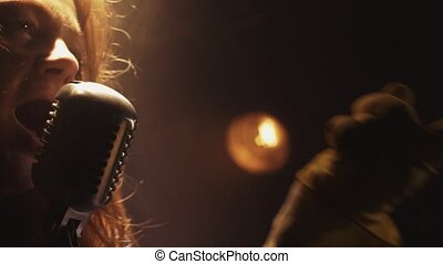 Scrubwoman sing in vintage microphone on stage. Emotions. Smoke. Spotlight.