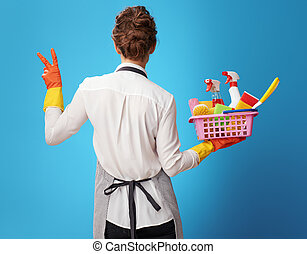 scrubwoman with a basket with detergents and brushes showing...