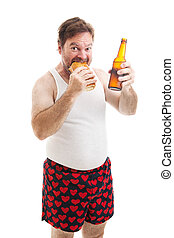 Scruffy, overweight middle aged man in his underwear, eating a submarine sandwich and drinking a beer. Isolated on white.