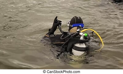 scuba diver enters the mountain lake water. practicing...