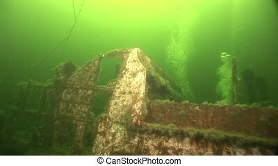Scuba diver near rusty wreckage shipwreck, White Sea Russia....