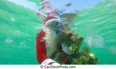 Scuba Santa Claus under water installs Christmas tree on seabed