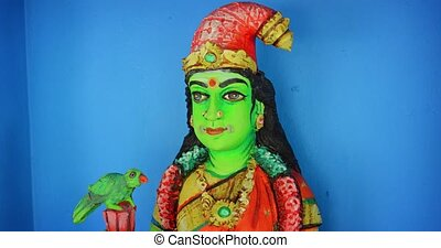 Hand sculpted and painted image of a hindu deity with green skin, holding a parrot, displayed inside a popular temple. 4k footage