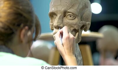 Sculptor at work. Woman working at the human head. - ...