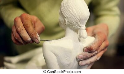 Sculptor corrects arm of female figurine by special tool