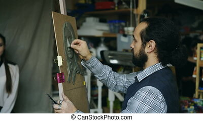 Sculptor creating sculpture of human's face on canvas while...