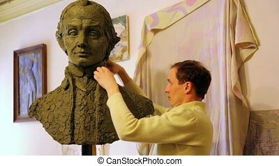 Sculptor Denis Petrov makes mold A.Suvorov bust of clay inside studio