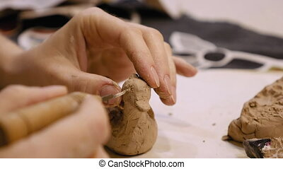 Sculptor is modeling clay figurine or statuette