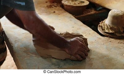 sculptor kneads clay with your hands - Potter kneads the...