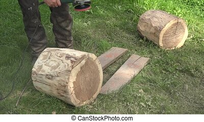 Sculptor prepare tree log wood for art work. Sanding bark...