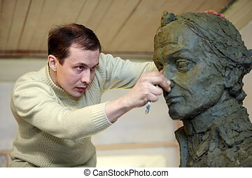 Sculptor works in the studio with a plasticine model of the bust of A.V. Suvorov - national hero of Russia.