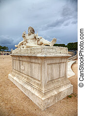 Sculpture in Tuileries gardens and dramatic sky in background, Paris, France.