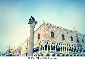 Sculpture of the winged lion, the Doges Palace and the St Mark's Basilica at St Mark`s Square in Venice.