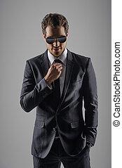 se, perfekt, in, hans, färsk, suit., tillitsfull, ung, affärsmän, in, solglasögon, betrakta kamera, medan, isolerat, på, grå