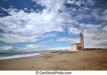 Sea and beach, long exposure shot, with a church