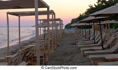 Sea and beach with empty sunbeds at sunset